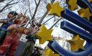 Изработени от папие маше фигури на момчета, които символизират рейтинговите агенции &quot;Муудис&quot;, &quot;Фич&quot; и &quot;S&amp;P&quot;, &nbsp;сякаш целят с прашка знака на еврото. Композицията беше представена &nbsp;преди началото на традиционния Розов понеделник на карнавал в Майнц, Германия.<br />