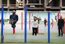 Китайците Жунчун и 76-годишният Хоу Индун са се отпуснали на специални приспособления на лостове в спортен комплекс