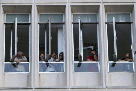 Служители гледат през прозорците в централата на ЕРТ. Не е ясно колко от тях ще бъдат съкратени.