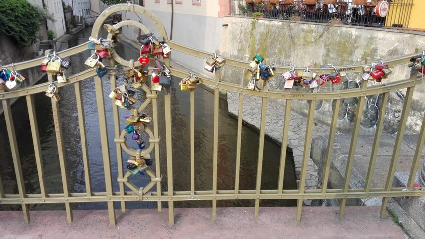 И в Прага началото на този обичай е поставено от рускоезичните, които са намерили втори дом там. Обикновенно на катинарите са изписани имената на младоженците, влюбените или просто някакво желание. След като се заключи катинара, ключа се изхвърля в реката (ако са младоженци, задължително от булката ...) Снимката е направена до прочутата морга, описана от Хашек в приключенията на Швейк (пада се в дясно, но не се вижда)